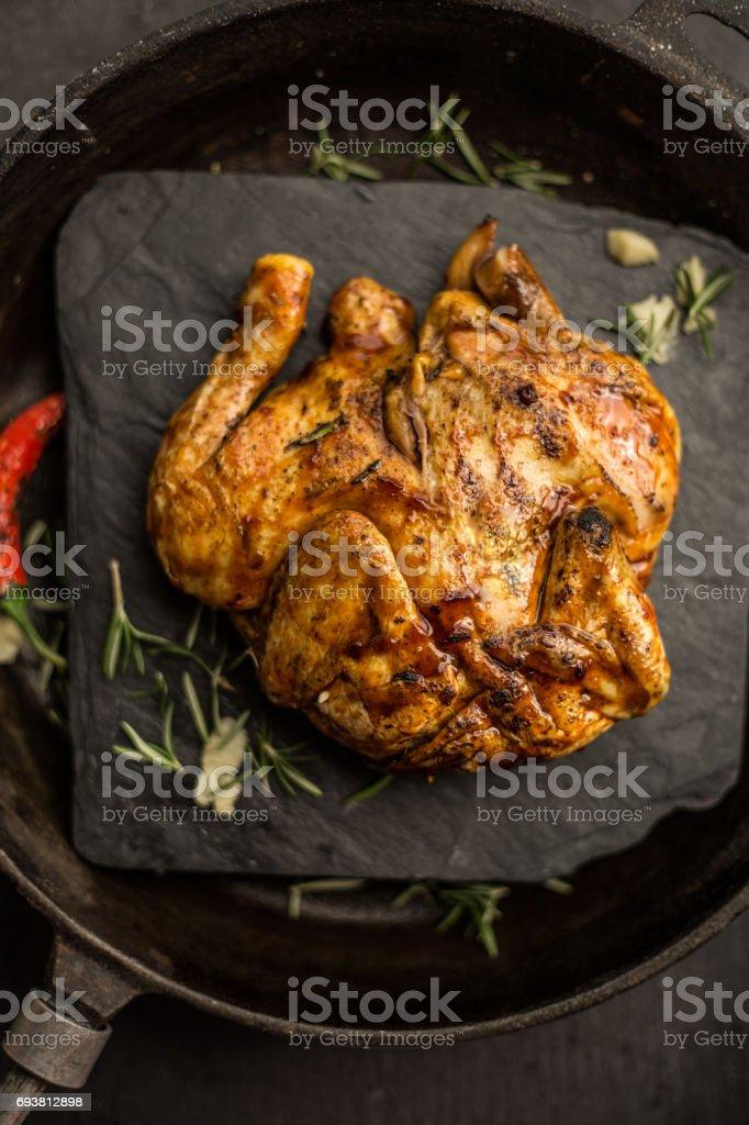 Whole raw corn chicken on dark pan. Restaurant. Top view