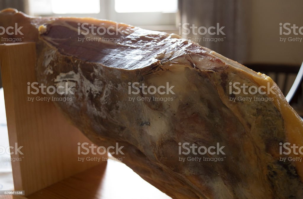 whole raw ham on the proper support stock photo