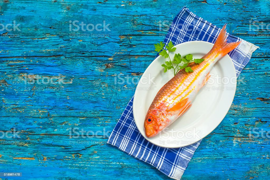 Whole red mullet wooden background stock photo