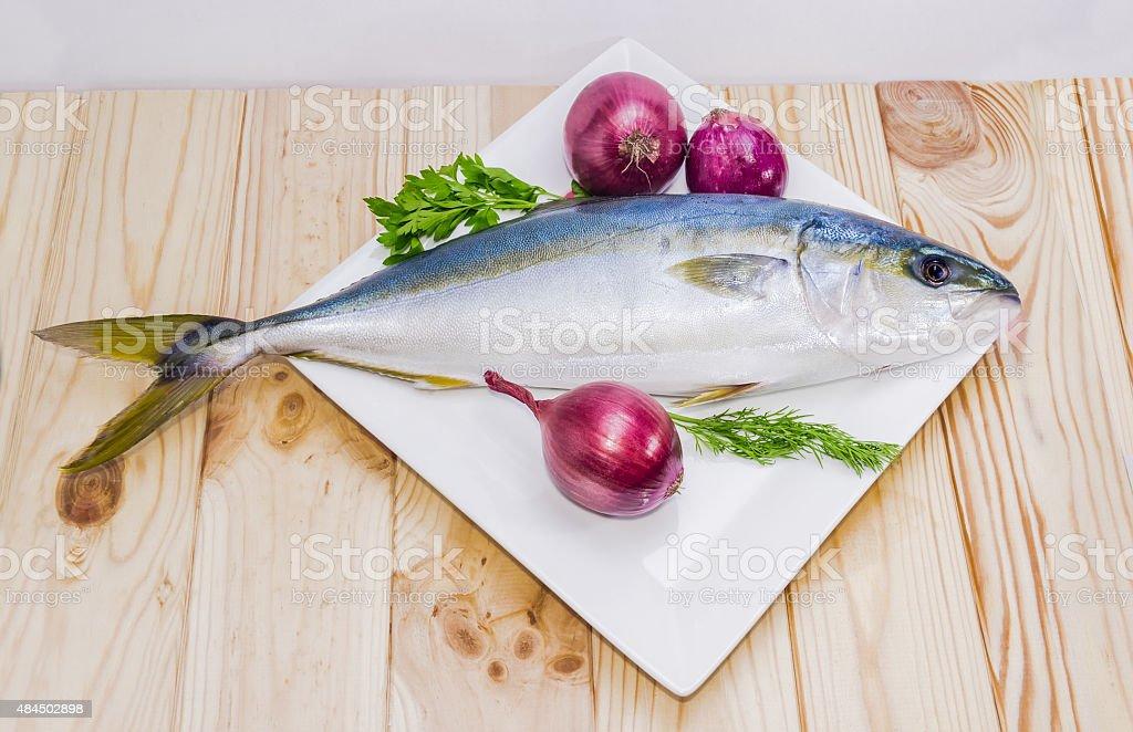 Whole round fish yellowtail and red onion stock photo