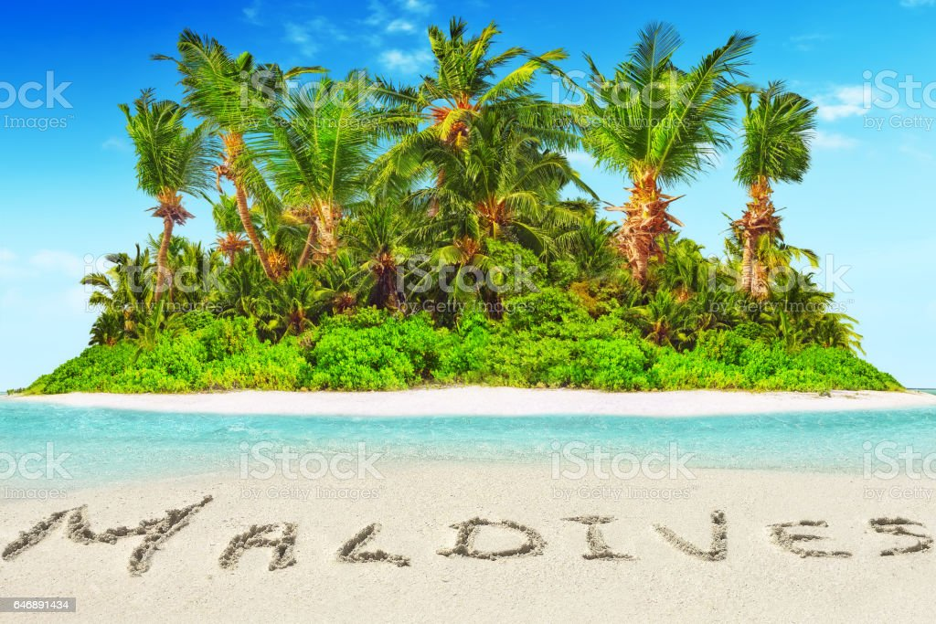 Whole tropical island within atoll in tropical Ocean and inscription 'Maldives' in the sand on a tropical island,  Maldives. stock photo