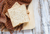 Whole wheat bread on white wooden table
