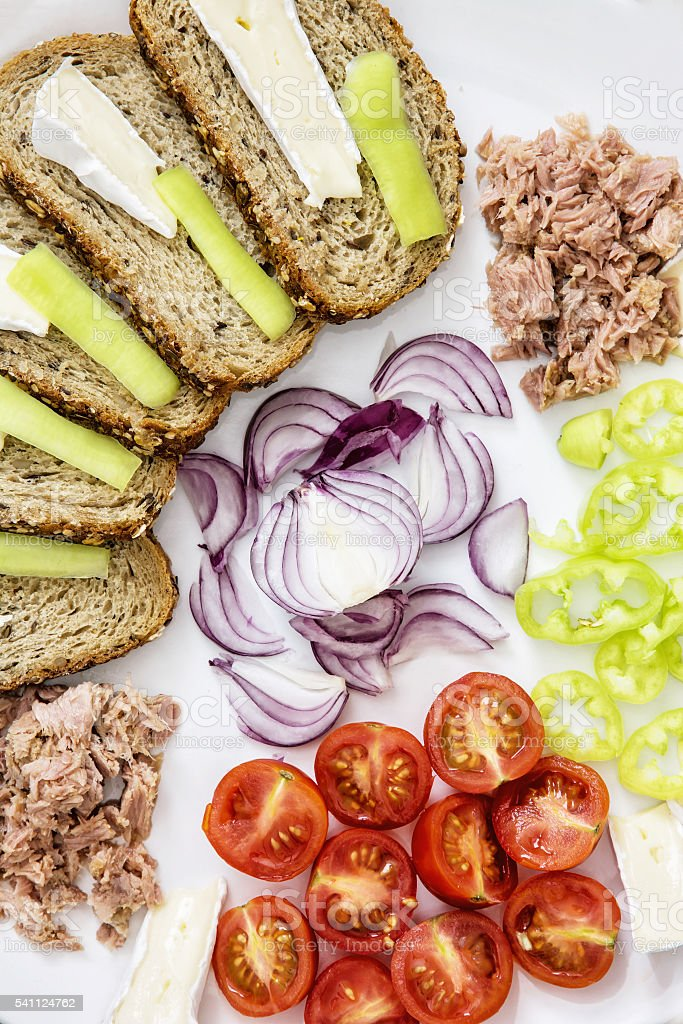 Whole wheat bread with cheese, paprika, tuna, onion and tomatoes stock photo