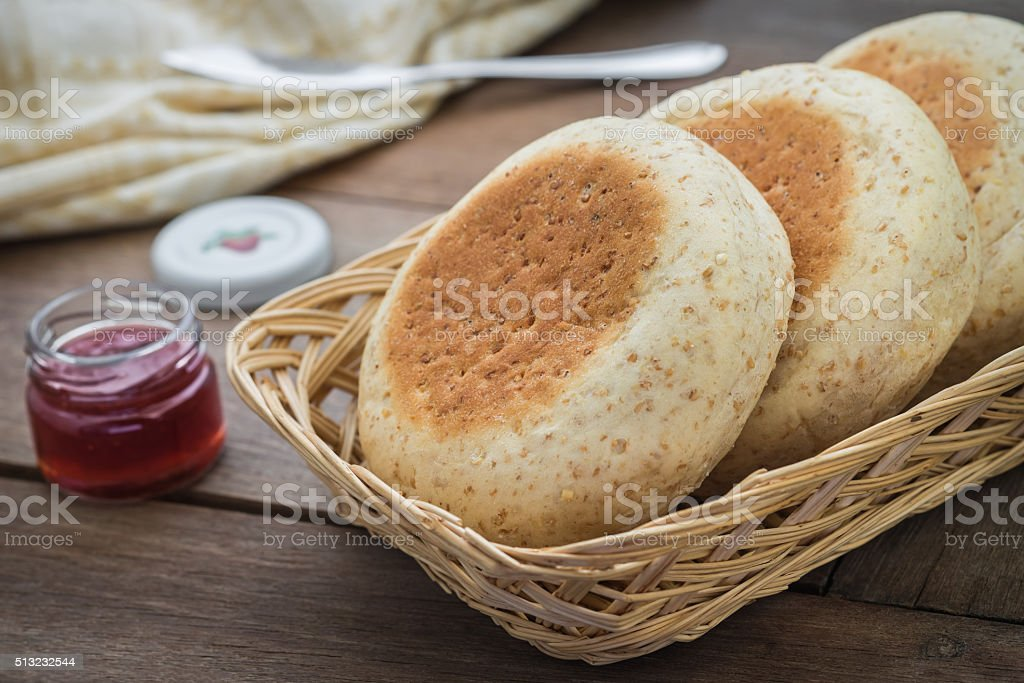 Whole wheat english muffins in basket and strawberry jam stock photo