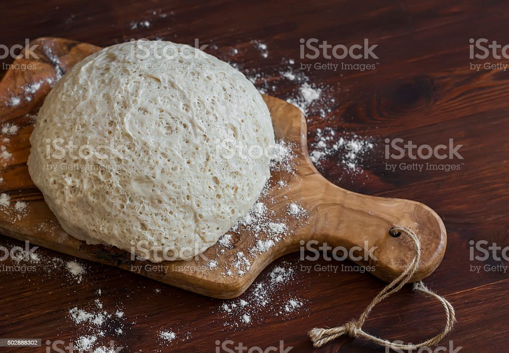Whole wheat flour the dough on an olive wood board. stock photo