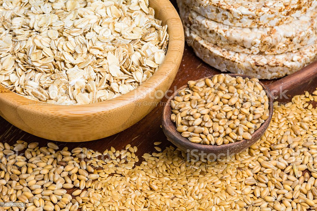 Whole wheat grains, oats and oat cakes stock photo