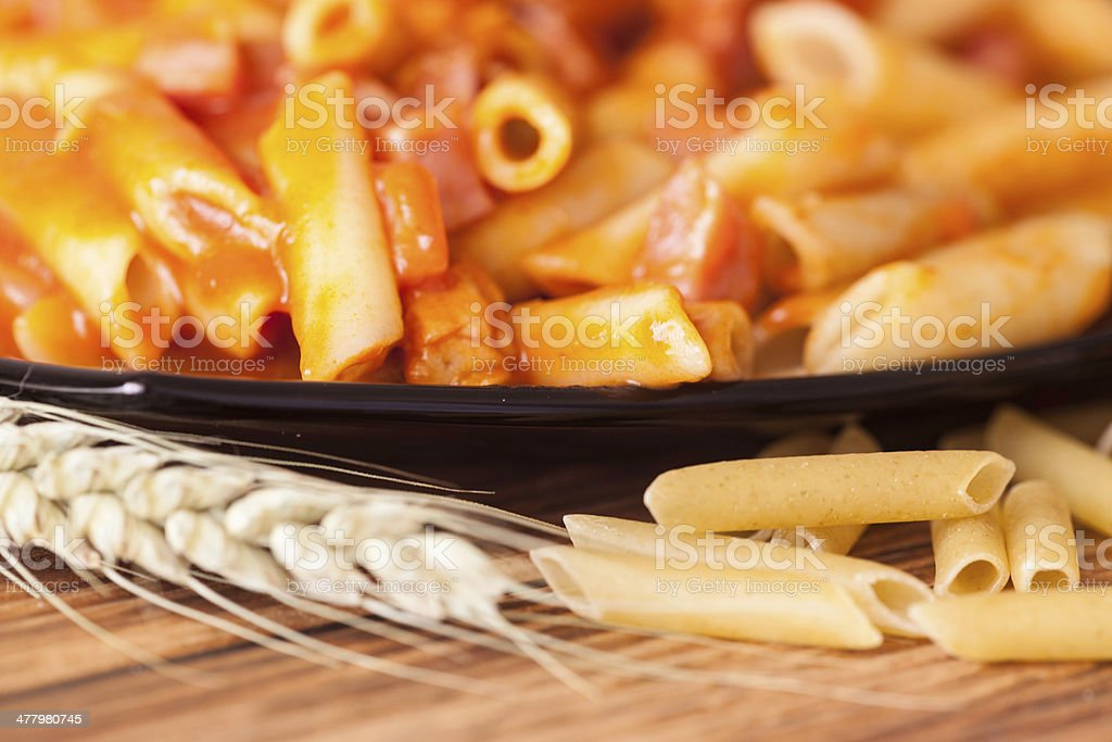 whole wheat pasta on a wooden table stock photo
