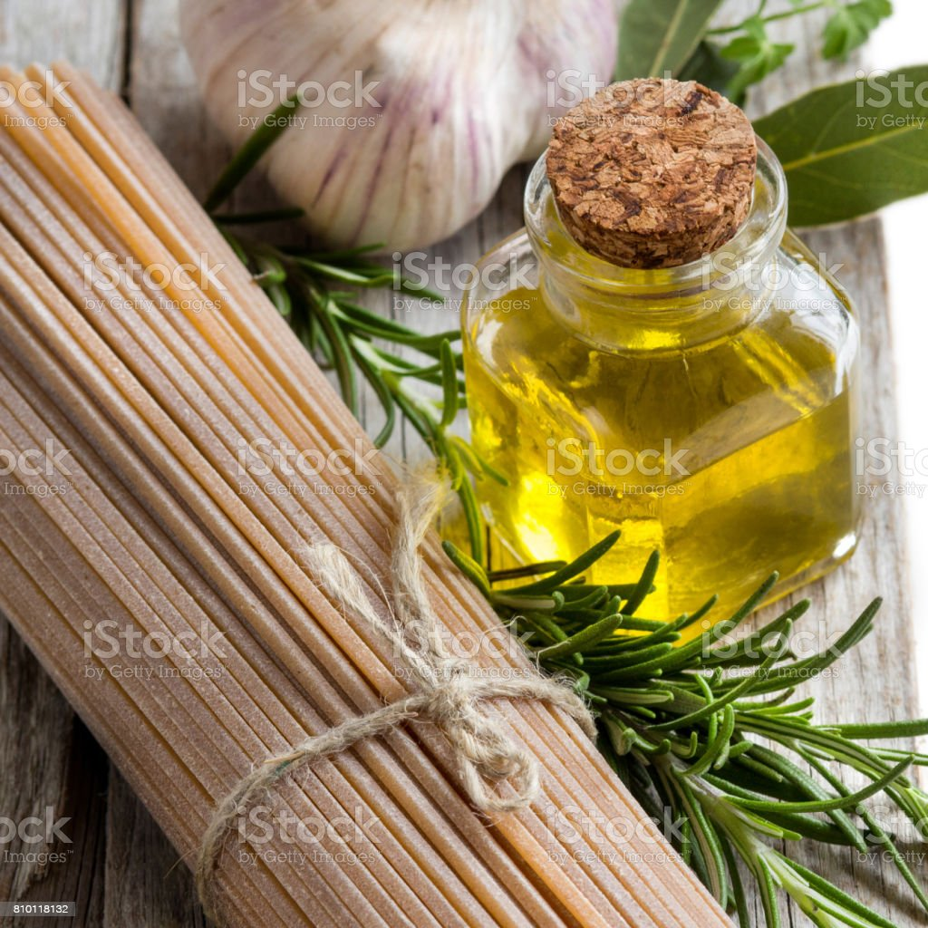 Whole wheat spaghetti, garlic, oilve oil and herbs stock photo
