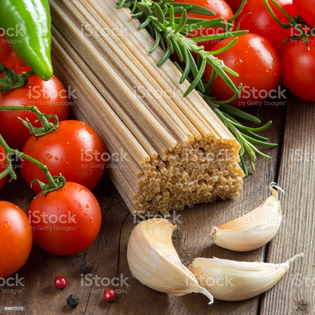 Whole wheat spaghetti, vegetables and herbs stock photo