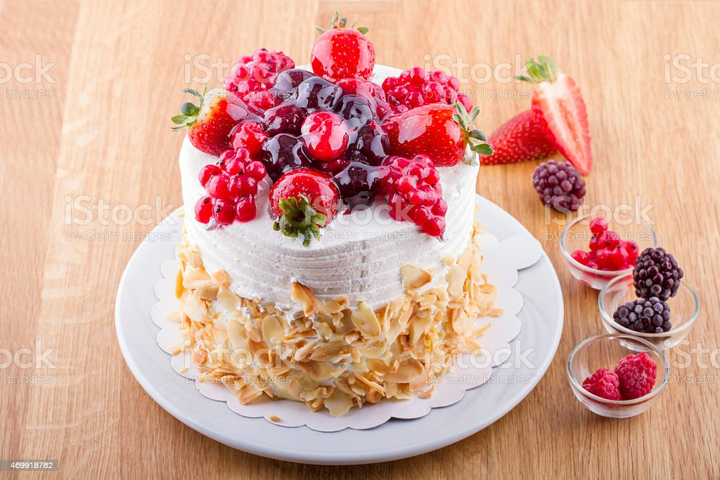 Whole White Berry Fruit Cake on Wooden Table stock photo