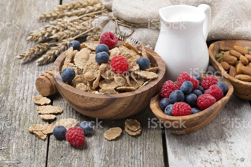 wholegrain flakes with fresh berries, nuts and milk stock photo