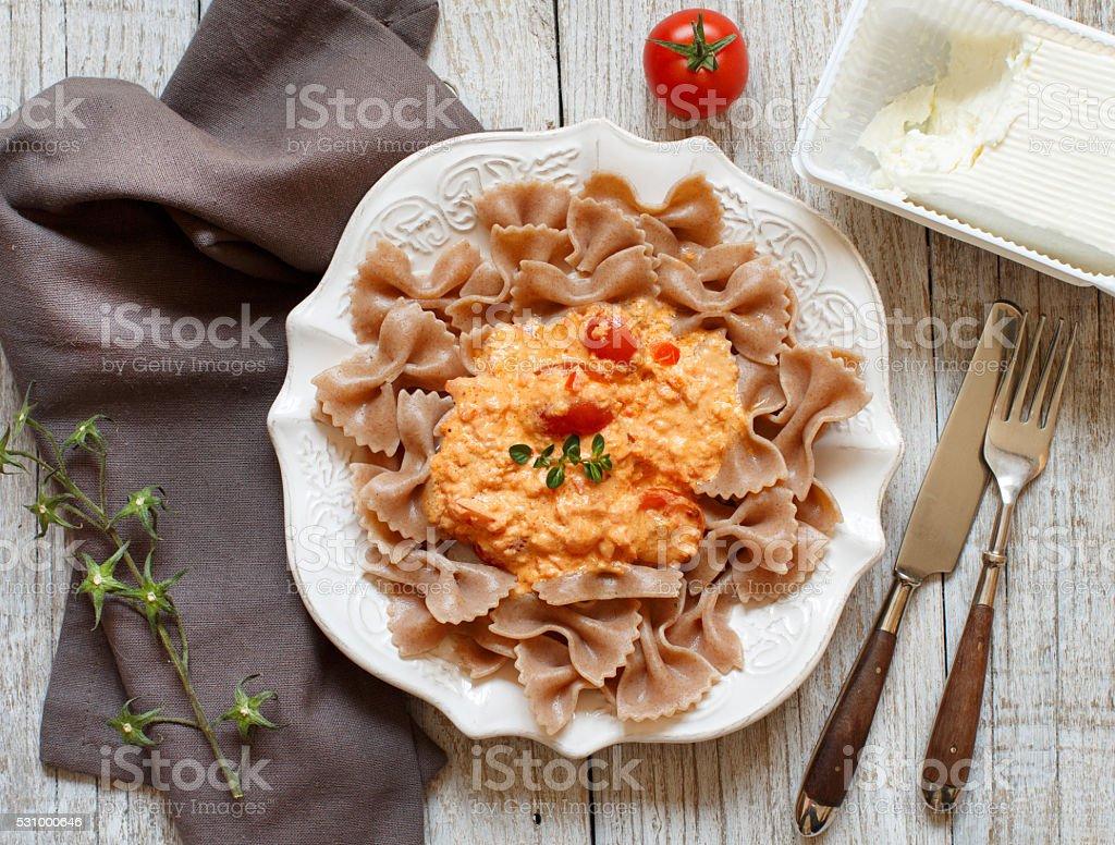 Wholegrain Pasta with stracchino cheese and fresh tomatoes stock photo