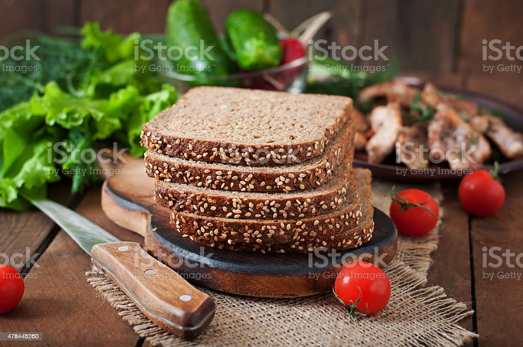 Wholegrain rye bread with bran and seeds on wooden table stock photo