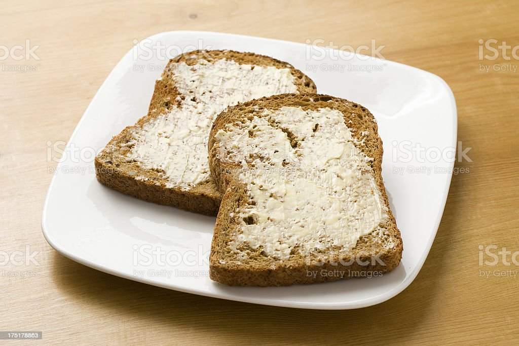 Wholemeal brown toast with butter on a plate royalty-free stock photo