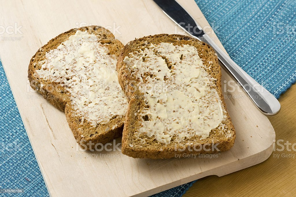 Wholemeal brown toast with butter on a wooden surface royalty-free stock photo