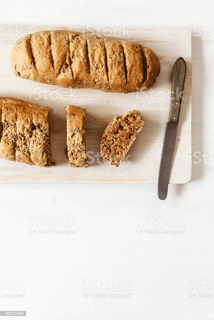 Wholemeal spelt baguettes on chopping board, knife stock photo