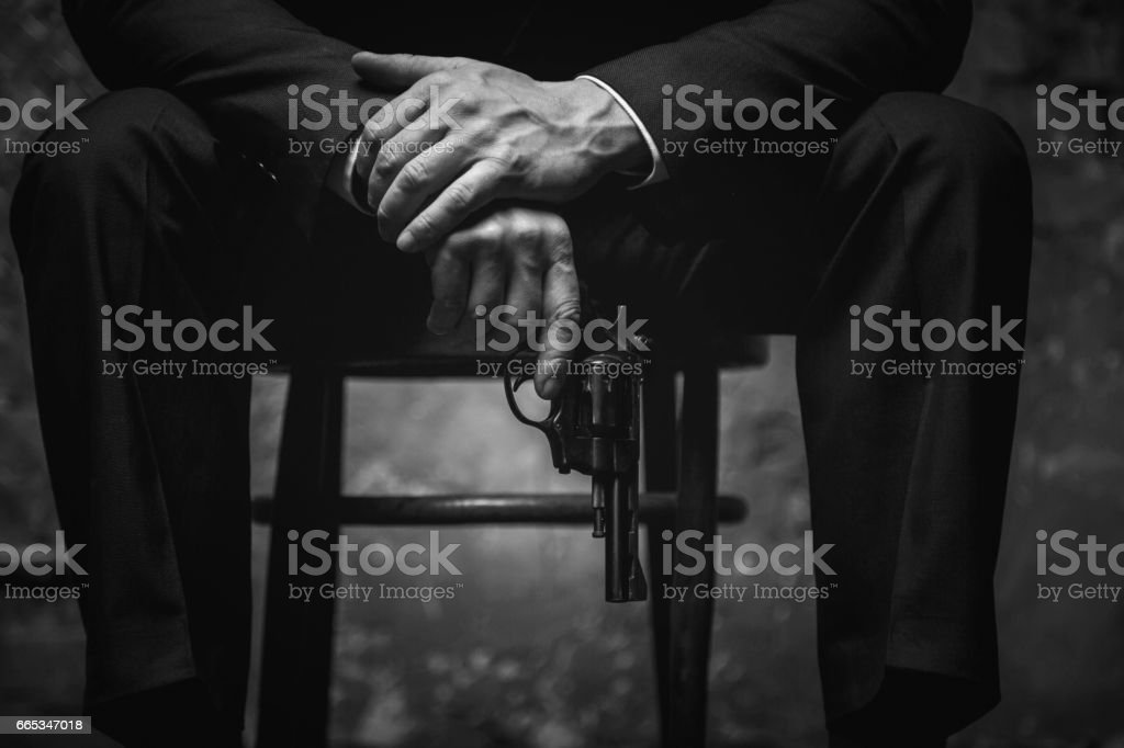Wicked man holding his gun at the ready stock photo