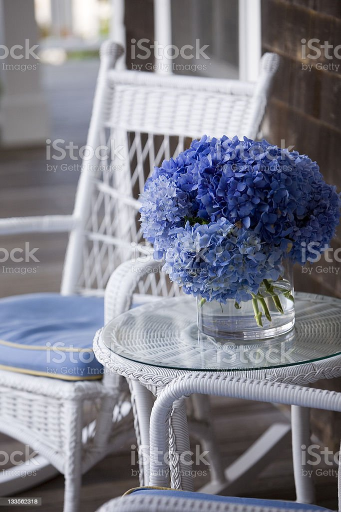 Wicker and blue Hydrangea  on a porch stock photo