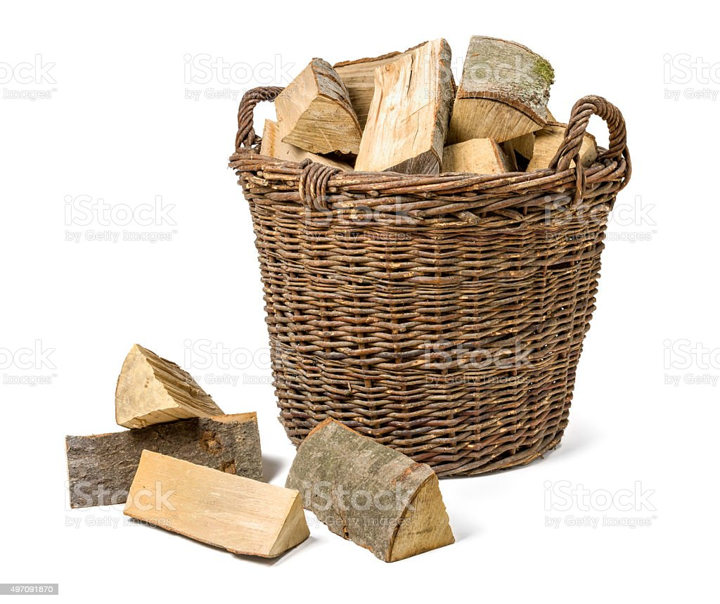 Wicker basket filled with firewood stock photo