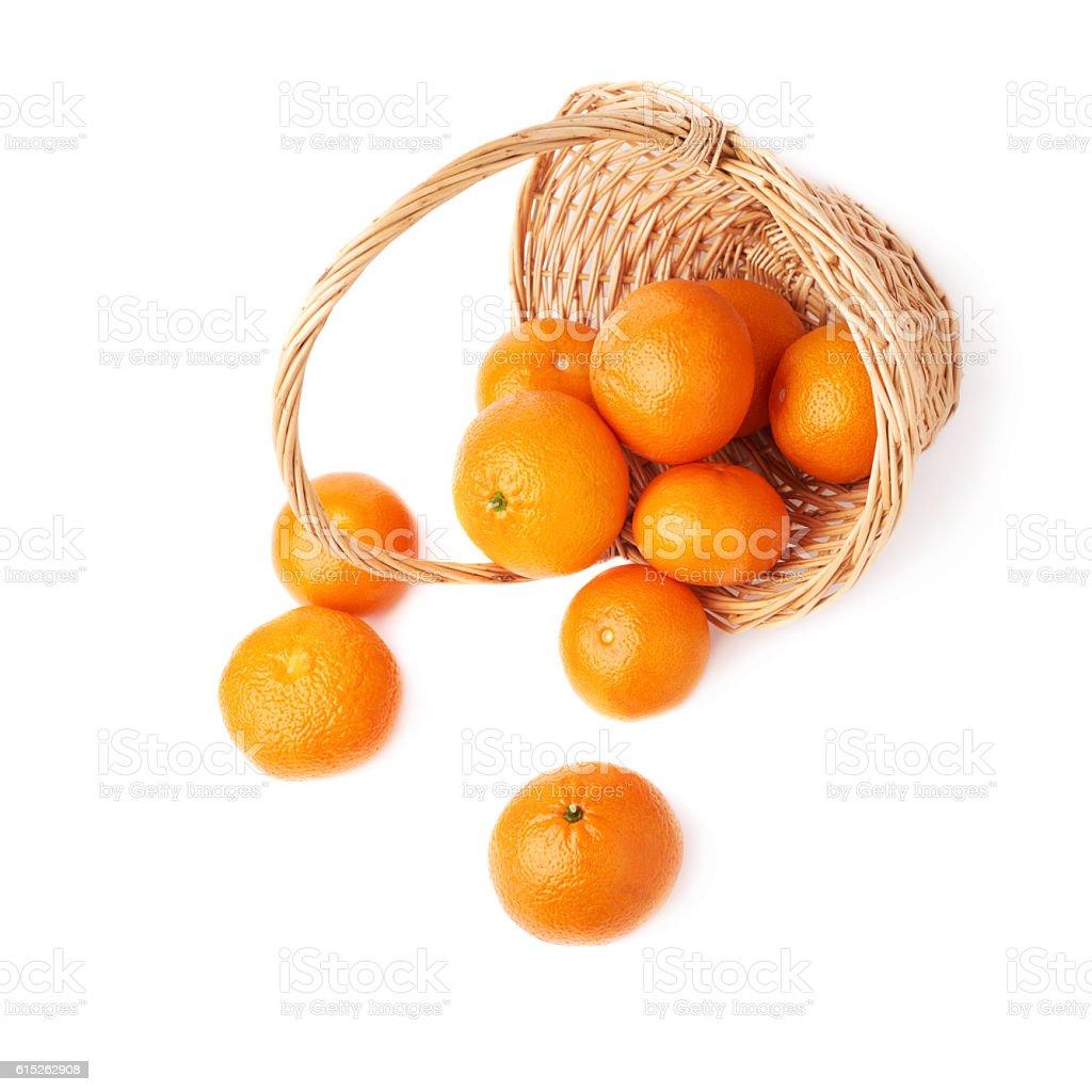 Wicker basket full of multiple ripe fresh juicy tangerines, composition stock photo