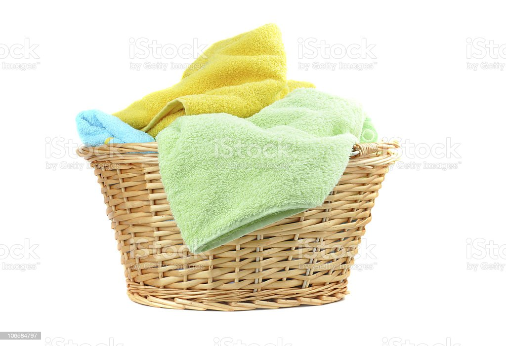 A wicker basket with colorful towels isolated on white stock photo