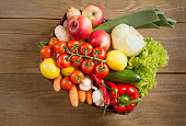 Wicker basket with fruits and vegetables on wooden table