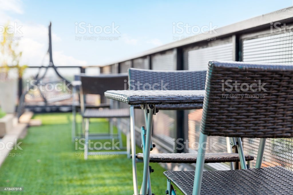 wicker chair  and a table on an open terrace stock photo