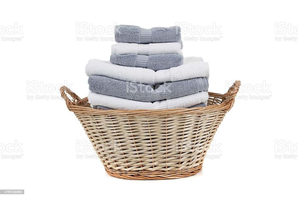 Wicker laundry basket full of white and gray towels stock photo