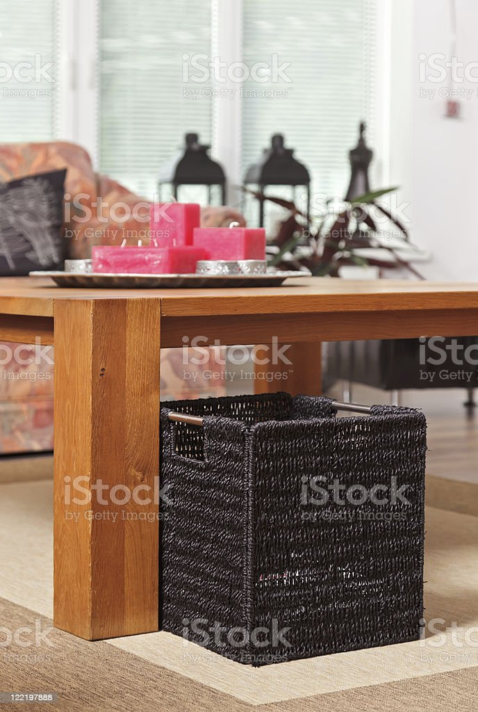 Wicker newspaper basket under wooden table stock photo