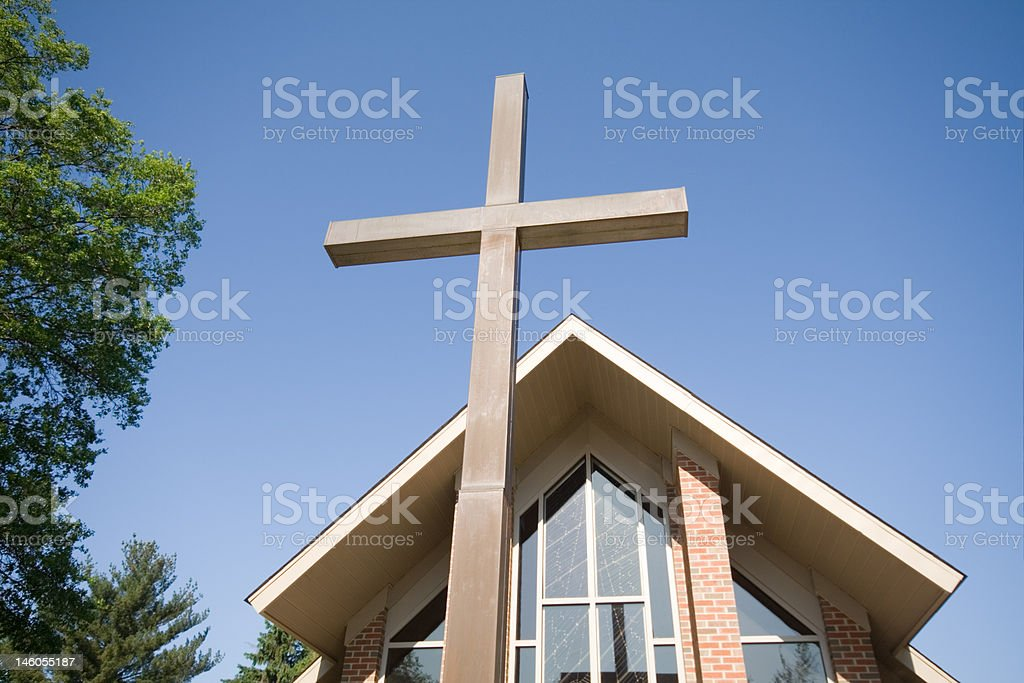 Wide Angle of Tall Cross with Modern Church in Background stock photo