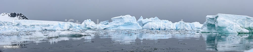 Wide angle panorama of Icebergs with reflections in Antarctica stock photo