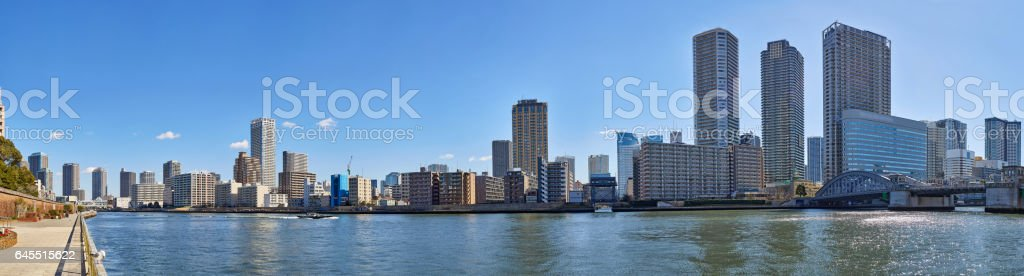 Wide angle panoramic view of winter Sumida river under blue sky in Tokyo with wavy water, boats, bridge and skyscrapers stock photo