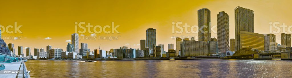 Wide angle panoramic view of winter Sumida river under spring sky in Tokyo with wavy water, boats, bridge and skyscrapers stock photo