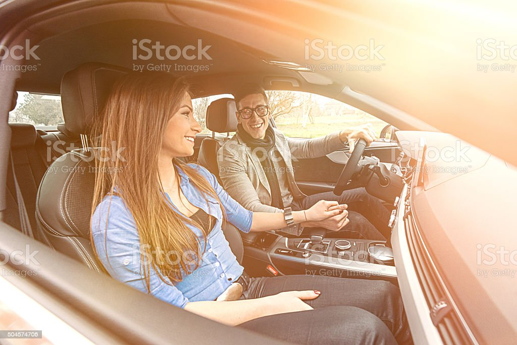 Wide angle portrait of attractive young couple driving luxury car stock photo