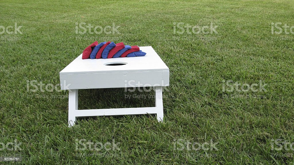 Wide angle shot of cornhole board and eight bags stock photo