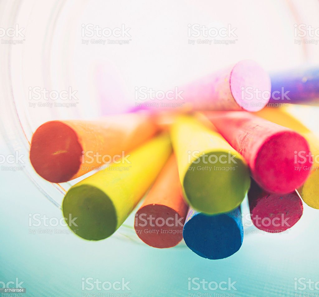 Wide angle view of colored chalks in a glass jar stock photo