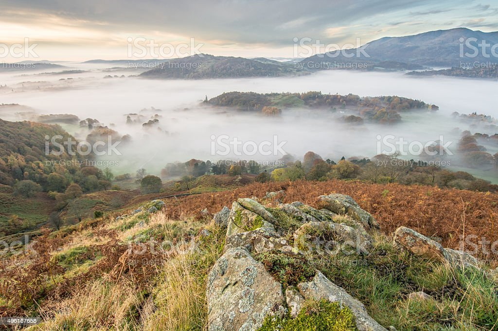 Wide Angle View Of Langdale Valley Covered In Autumn Fog. stock photo