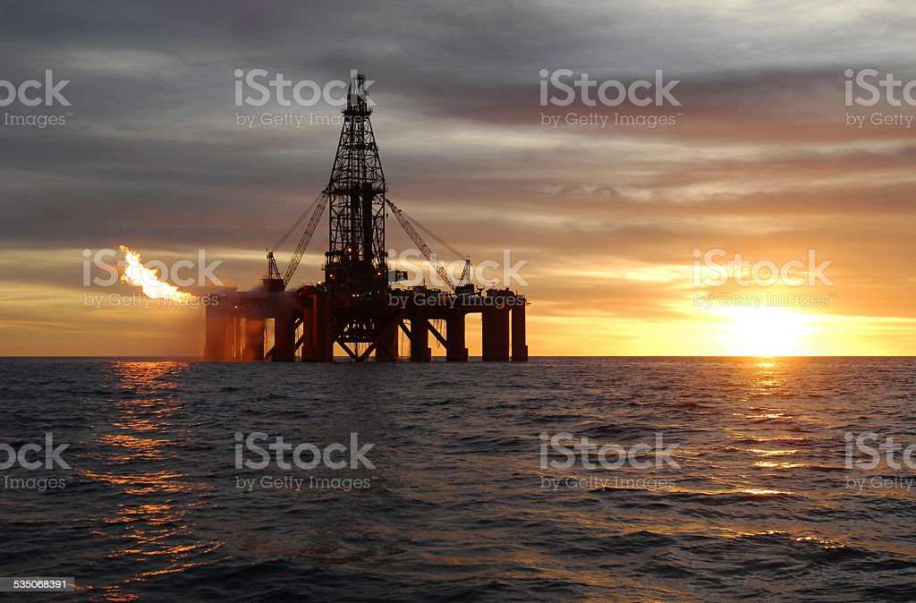 Wide angle view of ocean oil rig at sunset. stock photo
