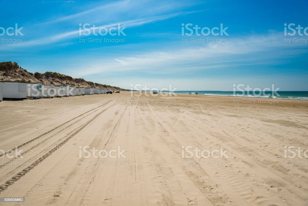 Wide beach with huts and cars stock photo