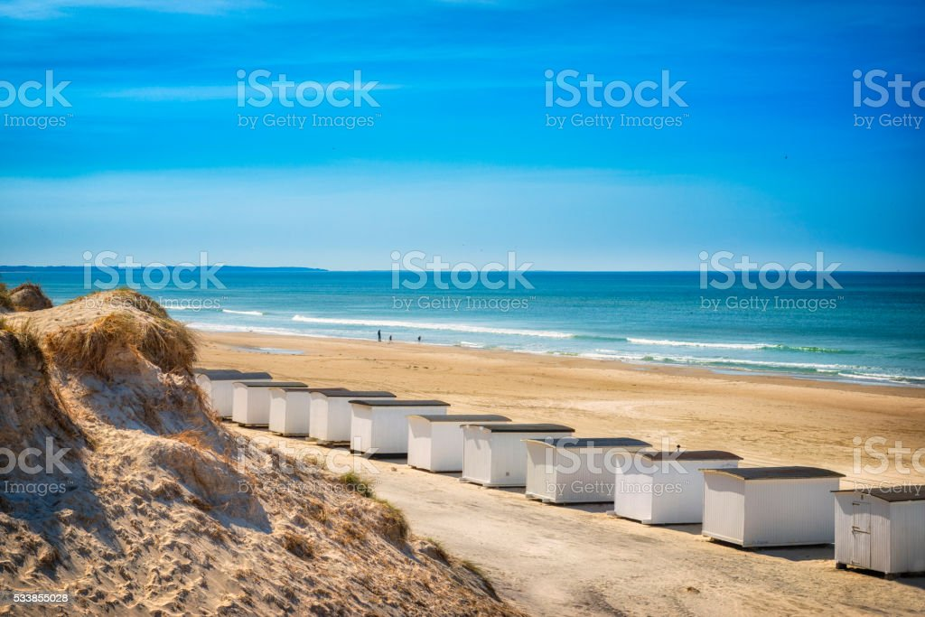 Wide beach with whithe huts stock photo