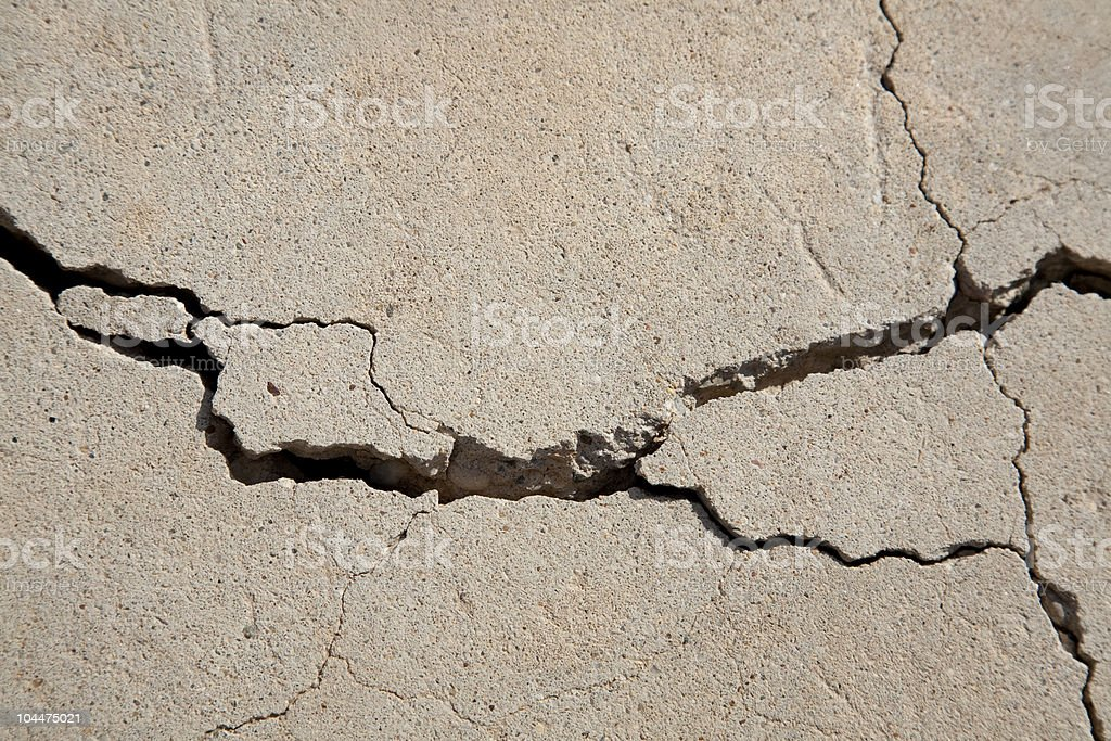 A wide crack in a slab of beige concrete stock photo