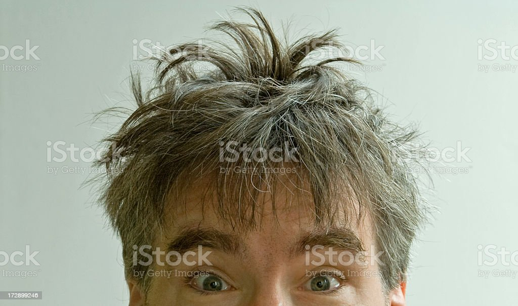 Wide eyed male with crazy bed head on white background stock photo