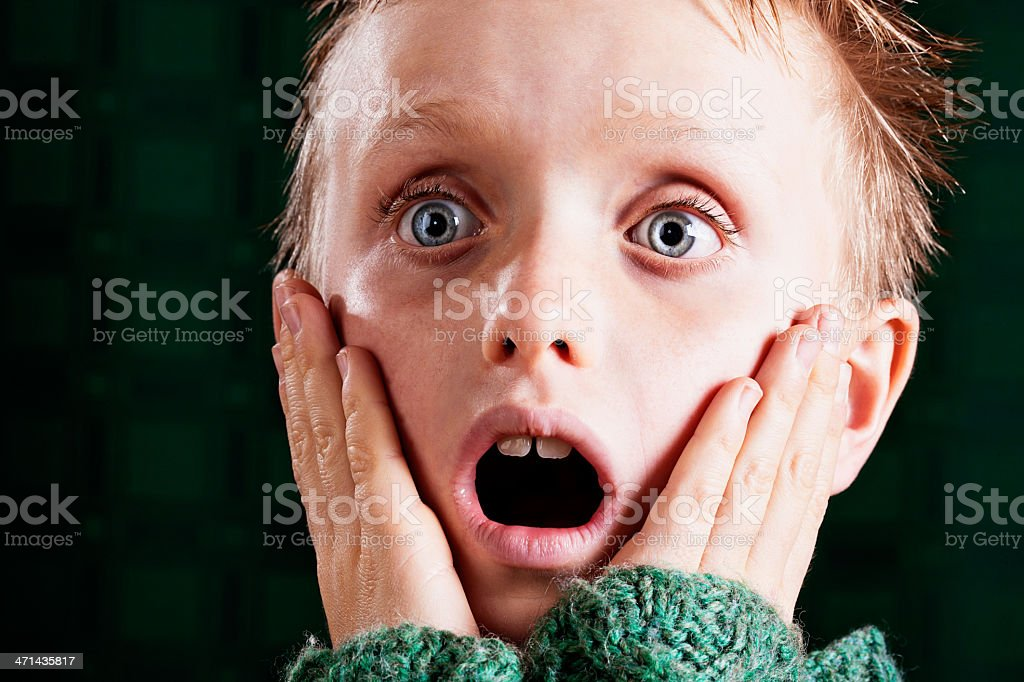 Wide eyed tearful little boy looks shocked and sad stock photo