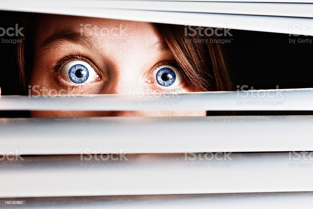 Wide eyed terrified young woman peeps through venetian blinds royalty-free stock photo