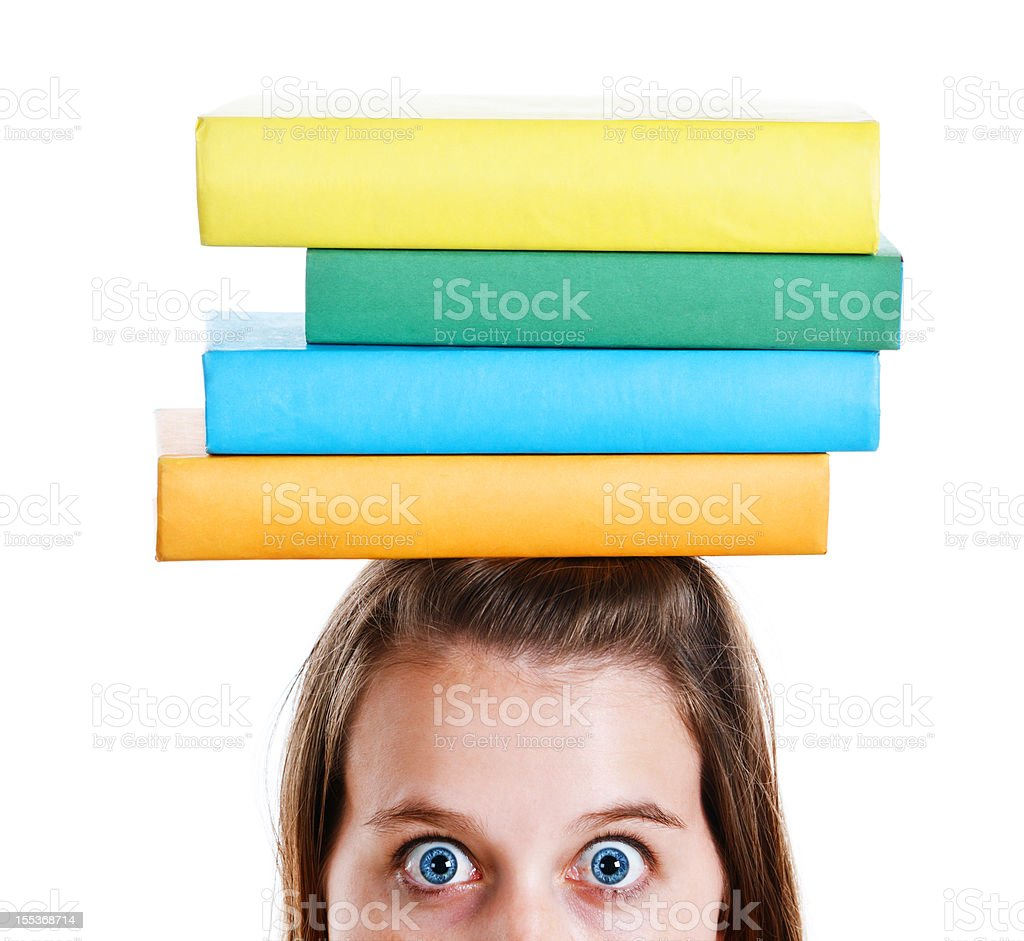 Wide eyed young woman balances books on head royalty-free stock photo