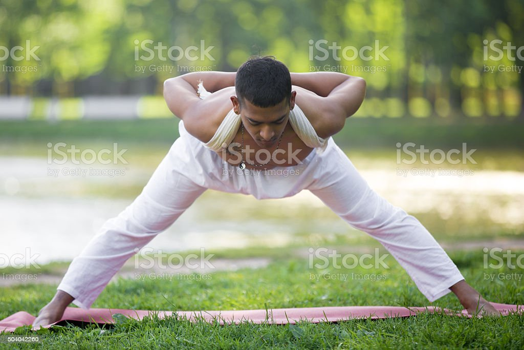 Wide Legged Forward Bend in park stock photo