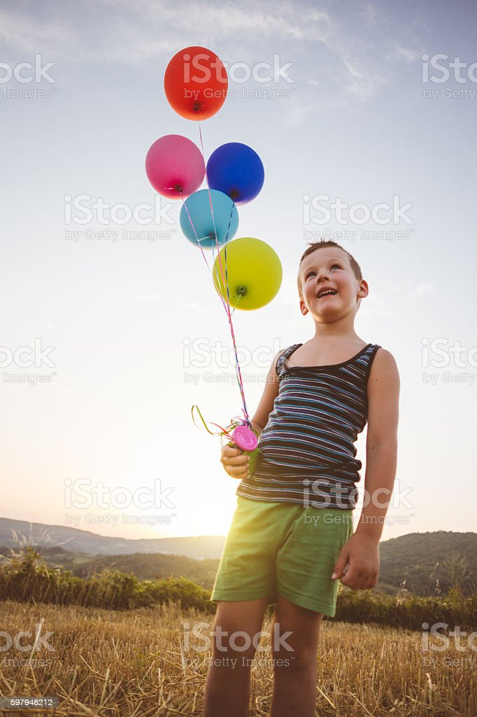 Wide open smile of lovely boy holding balloons stock photo