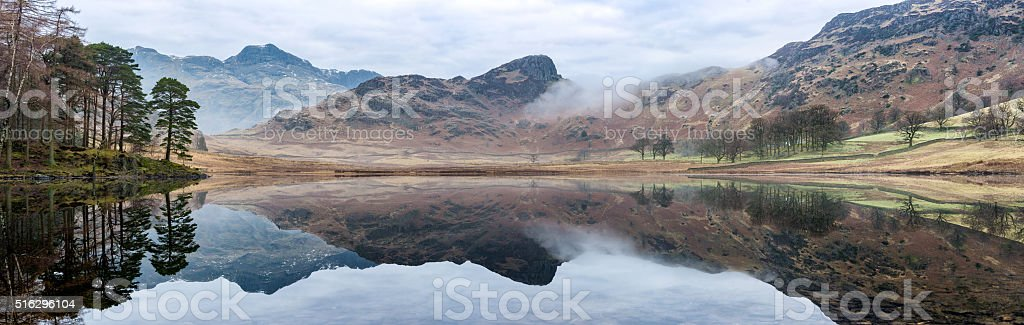 Wide Panorama At Blea Tarn With Reflections And Patchy Mist. stock photo