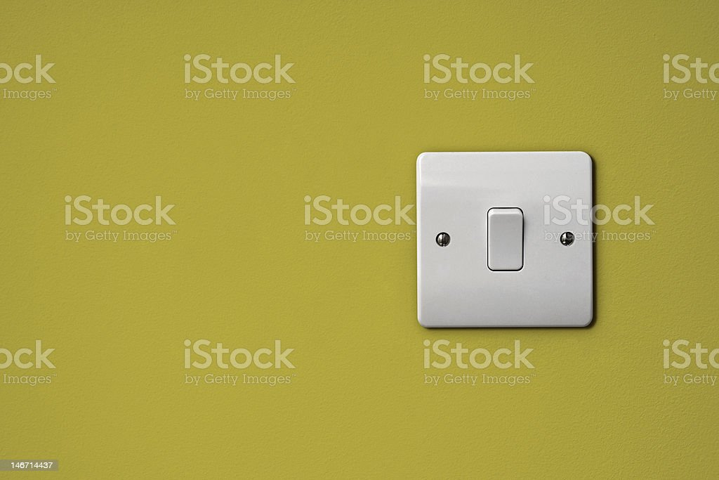 Wide plate white light switch on a chartreuse wall stock photo