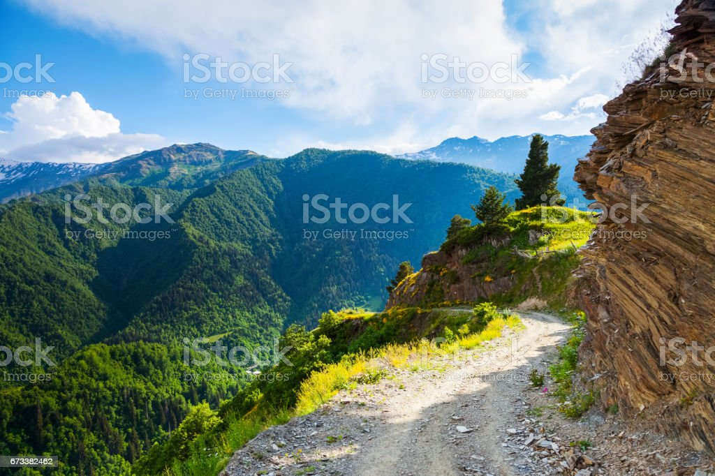 A wide road with a cliff leads down to the high Caucasus mountains covered with green forests on a sunny summer day. Upper Svaneti, Georgia, Europe. stock photo